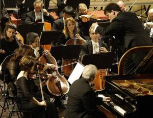 New York Philharmonic new music director Alan Gilbert, right, conducts the philharmonic in this file photo.