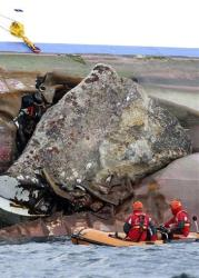 Firefighters on a dinghy look at a rock emerging from the side of the Costa Concordia, the day after it ran aground off the Tuscan island of Giglio, Italy, Sunday, Jan. 15, 2012.