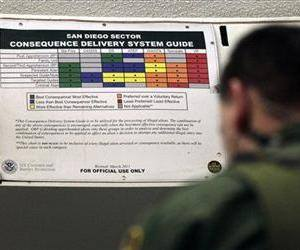 A Border Patrol agent works in front of a color-coded chart at a detention center  Wednesday, Jan. 11, 2012, in Imperial Beach, Calif.