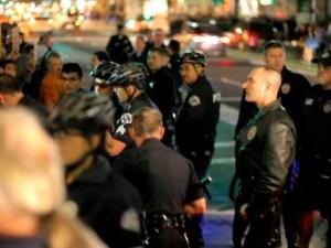 Crowd surrounds the arrest of a drummer during a protest in Los Angeles last week.