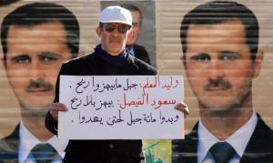 A Syrian government supporter holds a sign in front of pictures of President Bashar al-Assad during a pro-regime rally in Damascus Saturday.