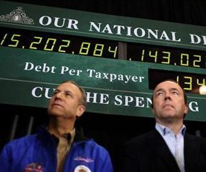 Supporters of Mitt Romney stand next to a national debt clock during a rally at Exeter High School on January 8, 2012 in Exeter, New Hampshire.
