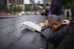 Eddie Reyes is comforted while remembering fifteen of his colleagues in the New York Police Department Emergency Service Unit who were killed on September 11, 2001.