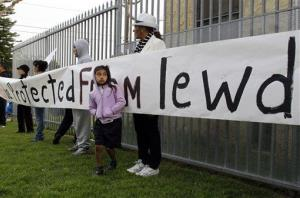 Ivis Urbina, right, with her granddaughter Alexa Agillon, 6, protest with others outside Miramonte Elementary school in Los Angeles yesterday.
