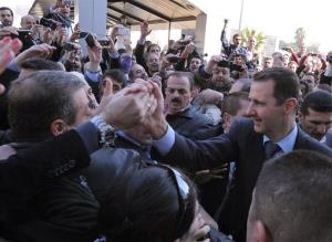 Syrian President Bashar Assad, right, greets his supporters after he casts his ballot at a polling station during a referendum on the new constitution, in Damascus, Syria, on Sunday Feb. 26, 2012.