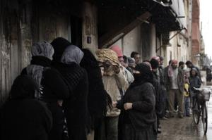 Syrians queue for bread outside a bakery in Qusayr, nine miles from Homs, on Thursday.