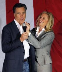 Ann Romney wipes lipstick off Mitt's face after kissing him at a campaign rally in Zanesville, Ohio, yesterday.