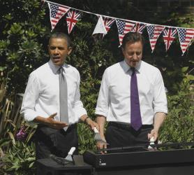 President Obama and British PM David Cameron work the grill as they visit with British and US service members and veterans at 10 Downing Street, Wednesday, May 25, 2011.