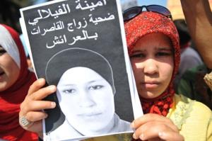 Amina  Filali's sister holds a poster of Amina during a  protest outside the court that approved her marriage.