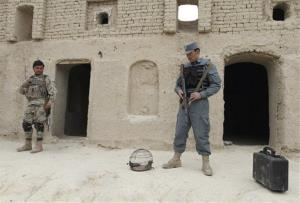 Afghan security forces stand guard outside one of the homes where Afghan civilians were killed last weekend.