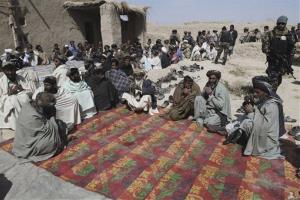 Afghan villagers pray during a prayer ceremony for the victims of Sunday's killing of civilians by a US soldier in Panjwai, Kandahar province south of Kabul, Afghanistan, Tuesday, March. 13, 2012.