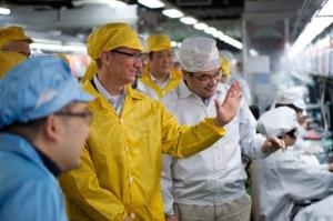 In this March 28 photo provided by Apple, CEO Tim Cook, center, visits the iPhone production line at Foxconn Zhengzhou Technology Park.