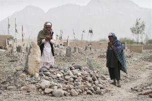 Afghan villagers pray over the grave of one of the 17 victims killed in the Panjwai rampage.