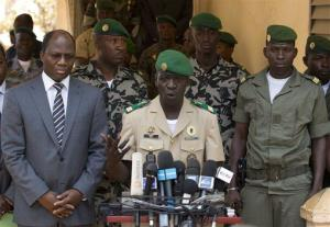 Coup leader Capt. Amadou Haya Sanogo, center, is accompanied by Burkina Faso Foreign Affairs Minister Djibril Bassole as he addresses the press at junta headquarters outside Bamako April 1, 2012.
