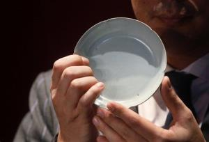 A Sotheby's official holds the 900-year-old Ruyao dish in Hong Kong.