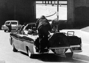 Secret Service agent Clint Hill stands on the back bumper of the presidential car after President Kennedy is shot.