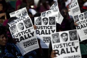 Members of the audience hold signs of support for Trayvon Martin during a rally in Miami last week.