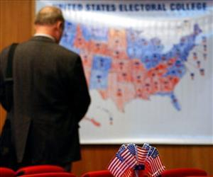 A man watches an electoral US map poster showing that Barack Obama has been elected president, early Wednesday, Nov. 5, 2008.