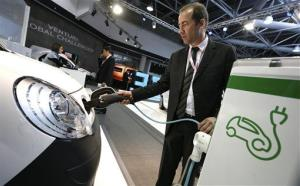 A man demonstrates the recharging of an electric car battery as he plugs in a Kangoo Renault electric car at a charging point  at the EVER exhibition in Monaco, Thursday, March 22, 2012.