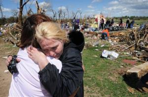 Sara Shogren, left, is hugged by Zoey Patrick as friends sort through the rubble of the Patrick's home, Sunday, April 15, 2012, in Marquette, Kans.