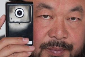 Artist Ai Weiwei holds a webcam that he was reportedly ordered by Chinese police to disconnect, at his home in Beijing on April 5, 2012.