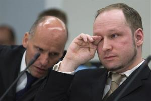 Norwegian Anders Behring Breivik, right, who is facing terrorism and premeditated murder charges, reacts as a video presented by the prosecution is shown in court, in Oslo.