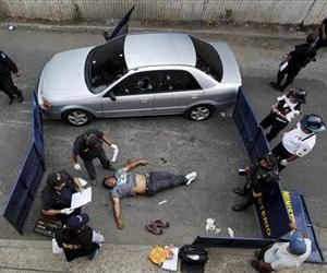 The body of a man shot to death lies in the street as investigators work the crime scene in Guatemala City,  Feb. 7, 2012.