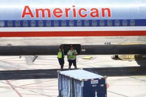 Two American Airlines ground crew workers stand under an airplane at Sky Harbor International Airport on April 19, 2012 in Phoenix, Arizona.