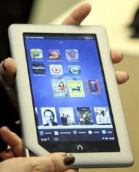 A demonstrator holds a Barnes & Noble Nook Tablet following a news conference in New York.