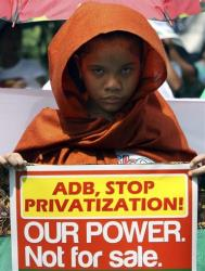 A protester holds a sign during a rally in Manila protesting the Asian Development Bank's role in privatizing utilities.