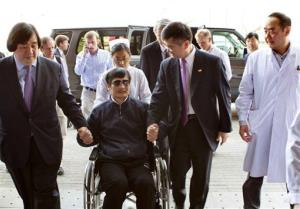 Chen Guangcheng is wheeled into a hospital by US Ambassador to China Gary Locke, right, and an unidentified official at left, in Beijing yesterday.
