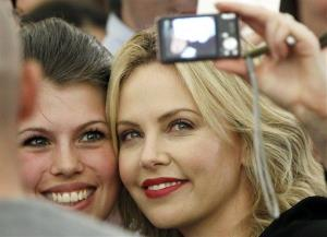 Actress Charlize Theron, right, takes a photo of herself with an unidentified fan during a photocall for the movie 'Snow White And The Huntsman' in Berlin, Germany, Wednesday, May 16, 2012.