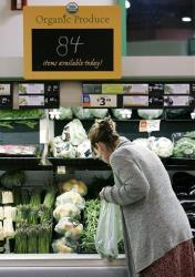 A customer picks out vegetables while shopping at the Hannaford Supermarket in Quincy, Mass., Friday morning, June 15, 2007.