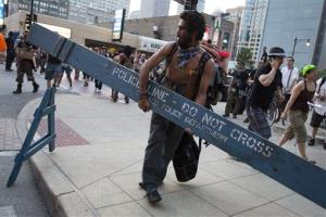 An anti-NATO protestor commandeers a police barricade during a march yesterday in Chicago.