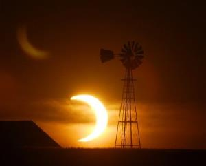 The sun sets behind a barn and windmill southwest of Ellis, Kansas, during a partial solar eclipse.