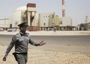 In this  Saturday, Aug. 21, 2010, file photo, an Iranian security directs media at the Bushehr nuclear power plant, outside the southern city of Bushehr, Iran.