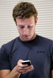 Mark Zuckerberg checks his cell phone after a product announcement at Facebook headquarters in Palo Alto, Calif.