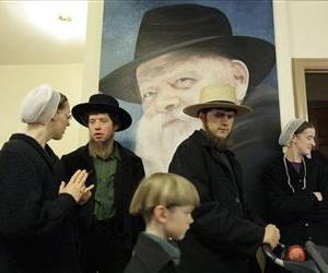 People walk in front of a portrait of the late Lubavitcher Rabbi Menachem Schneerson in Brooklyn, New York, March 31, 2009. Schneerson once said that Haifa had precious gems hidden beneath it.