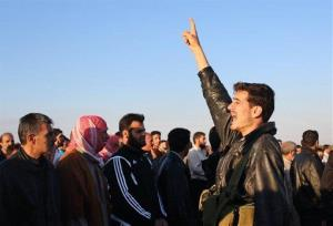 This citizen journalism image provided by Shaam News Network shows a Syrian rebel shouting slogans after the bodies of factory workers were found in Homs.