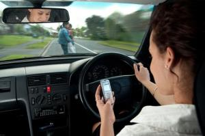 A stock photo of a person texting while driving.