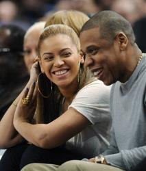Jay-Z reacts with his wife, Beyonce, left, during the third quarter of an NBA basketball game between the New York Knicks and New Jersey Nets, Feb. 20, 2012, at Madison Square Garden in New York.
