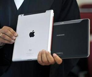In this Aug. 25, 2011 file photo a lawyer holds an Apple iPad and a Samsung Tablet-PC at a court in Duesseldorf, Germany.