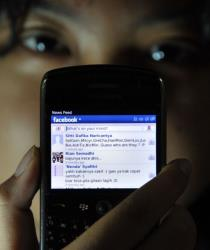 A girl shows her Facebook 'wall' on her mobile device in Jakarta on February 2, 2012.