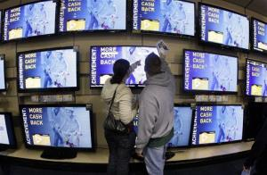 Shoppers look at televisions displayed at a Best Buy store after a midnight opening on Friday, Nov. 25, 2011, in Brentwood, Tenn.