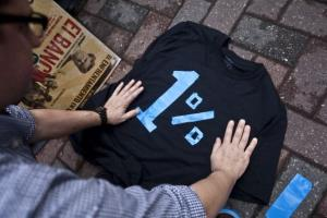 Han Shan, an Occupy Wall Street protester, makes a 1 percent shirt while protesting outside of the annual Bank of America Corp. shareholders meeting on May 9, in Charlotte, NC.
