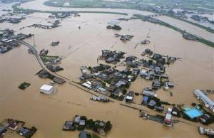 Houses are half submerged after water broke Yabe River's embankment, top, in Yanagawa, Fukuoka Prefecture, Japan, Saturday, July 14, 2012.