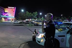 An Aurora police officer talks on his radio outside of the Century 16 theater on July 20.