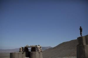 In this Tuesday, May 22, 2012 photo, an Afghan National Army soldier stands atop a perimeter wall overlooking the Chinari outpost in Logar province, east Afghanistan.