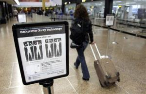 A passenger walks past a sign informing travelers about the use of full-body scanners at Seattle-Tacoma International Airport.