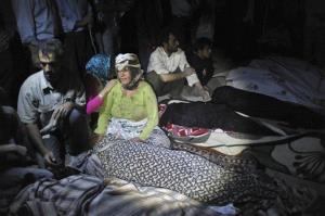 Victims of an earthquake sit over the bodies of their loved ones who were killed in the city of Varzaqan in northwestern Iran, on Saturday, Aug. 11, 2012.